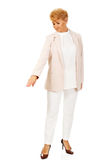 Ältere Geschäftsfrau des Lächelns, die für copyspace oder etwas zeigt Lizenzfreies Stockfoto