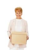 Ältere Geschäftsfrau des Lächelns, die Pappschachtel hält Stockfoto