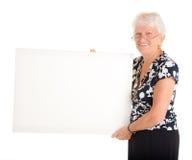 Ältere Geschäftsfrau, die ein unbelegtes Zeichen anhält Stockbilder