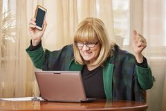 Ältere Geschäftsfrau, die fantastische Nachrichten empfängt Stockfotografie