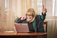 Ältere Geschäftsfrau, die fantastische Nachrichten empfängt Stockbilder