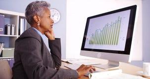 Ältere Geschäftsfrau, die am Telefon spricht und Computer verwendet Stockbilder