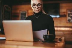 Ältere Geschäftsfrau, die wenige Dokumente am Café wiederholt stockbild