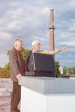 Ältere Geschäftsmänner, die Geschäft auf dem Dach eines Gebäudes besprechen Stockbilder