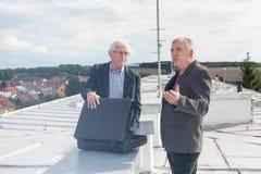 Ältere Geschäftsmänner, die Geschäftsvereinbarung auf dem Dach eines bui besprechen Lizenzfreies Stockfoto