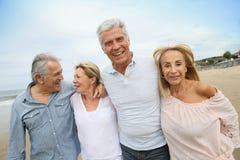 Ältere glückliche Menschen, die auf sandigen Strand gehen Stockbild