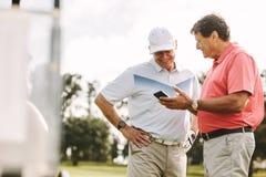 Ältere Golfspieler, welche die Ergebnisse am Telefon nach dem Spiel schauen stockbild