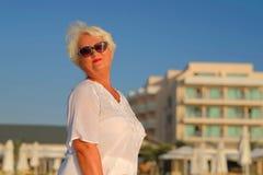 Ältere graue behaarte Frau, die nahes Gebäude bleibt stockfoto