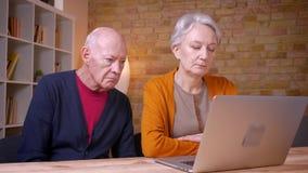 Ältere grauhaarige kaukasische Paare, die Inhalt im Laptop absorbierend und an Büro interessiert besprechen stock footage