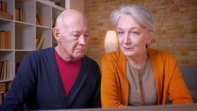 Ältere grauhaarige kaukasische Paare, die Inhalt im Laptop im Büro besprechen stock video footage