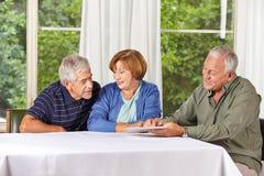 Ältere Gruppe, die Tablette PC betrachtet Stockbild