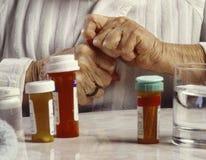 Ältere Hände, die mit Pilleflasche kämpfen Stockbild