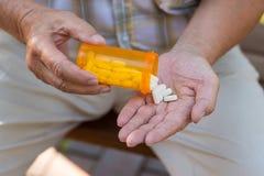 Ältere Hand hält Pillen stockbilder