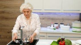 Ältere Hausfrau Washing Vegetables In die Wanne stock footage
