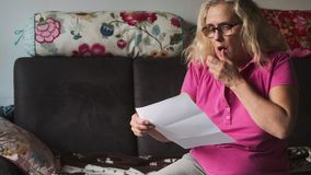 Ältere Haushaltsfrau öffnet einen Brief und wird bestimmt auf eine negative Art durch die hohe Nachfrage von Geld w entsetzt und  stock video footage