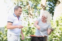 Ältere Heirat, die zusammen Fleisch grillt Lizenzfreies Stockfoto