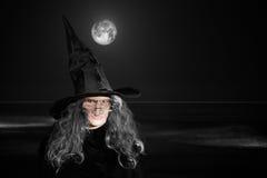 Ältere Hexe im schwarzen Hut - Wellen u. Vollmond Stockbild