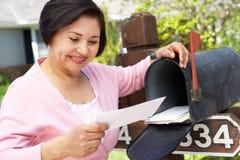 Ältere hispanische Frau, die Briefkasten überprüft Stockfoto