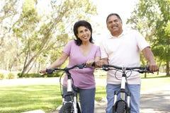 Ältere hispanische Paar-Reitfahrräder im Park stockfotos