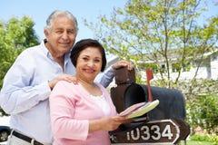 Ältere hispanische Paare, die Briefkasten überprüfen Stockfotos