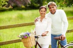Ältere indische Paare auf Zyklus-Fahrt in der Landschaft Stockbilder