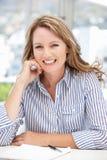 Ältere Karrierefrau gesessen am Schreibtischlächeln Lizenzfreie Stockbilder