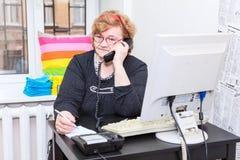 Ältere kaukasische Frau, die um Telefon im Büroraum ersucht Stockfotos