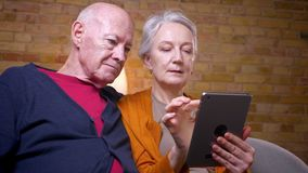 Ältere kaukasische Gatten, die zusammen den App auf der Tablette sitzt am Sofa im Wohnzimmer verwenden stock video