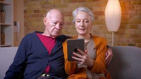 Ältere kaukasische Gatten, die zusammen Tablette verwenden und am Sofa im Wohnzimmer sitzen stock video