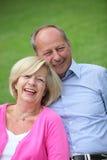 Ältere kaukasische Paare, die zusammen draußen lachen Lizenzfreie Stockfotos