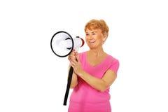 Ältere lächelnde Frau, die durch ein Megaphon schreit Stockbild