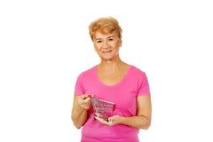 Ältere lächelnde Frau, die kleine Laufkatze hält Lizenzfreies Stockfoto