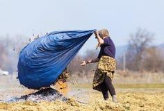 Ältere ländliche Frau, die gefallene Blätter brennt Lizenzfreie Stockfotografie