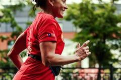 Ältere Läuferfrau, die auf Stadtstraßen läuft lizenzfreies stockfoto