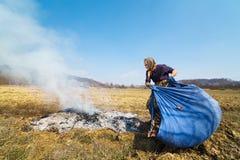 Ältere landwirtschaftliche Frau, die gefallene Blätter brennt Stockbilder
