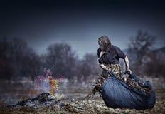 Ältere landwirtschaftliche Frau, die gefallene Blätter brennt Stockfotos