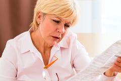 Ältere Lesung mit Presbyopiebeipackzettel Stockfoto