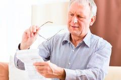 Ältere Lesung mit Presbyopiebeipackzettel stockbilder