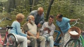 Ältere Leute betrachten den Schirm der Tablette im Park
