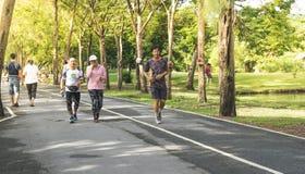 Ältere Leute, die in grünen Park in der Stadt laufen lizenzfreie stockbilder