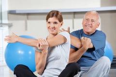 Ältere Leute, die in Gymnastik ausdehnen Stockfotografie