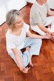 Ältere Leute, die im Yoga meditieren Lizenzfreies Stockfoto