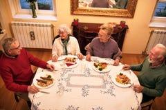 Ältere Leute genießen und lächelnd beim Essen des Abendessens an der Pflege von h lizenzfreie stockfotos