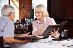 Ältere Leute mit Menü lizenzfreie stockfotos