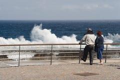 Ältere Leutetouristen beobachten Wellen, auf einem Pier zu zerquetschen stockfoto