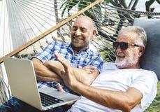 Ältere Männer, die auf einer Hängematte unter Verwendung eines Laptops liegen stockfotografie