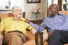 Ältere Männer, die in den Lehnsesseln sich entspannen Stockfoto