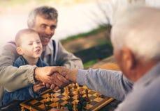 Ältere Männer, die Spaß haben und Schach am Park spielen Lizenzfreies Stockfoto
