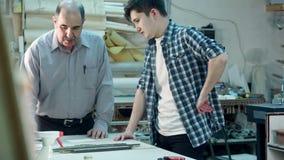 Ältere männliche Arbeitskraft, die jungem Auszubildendem zeigt, wie man einen Rahmen hinter dem Schreibtisch in der Rahmenwerksta stock video