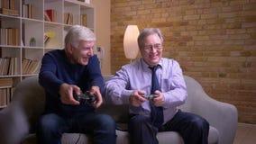 Ältere männliche Freunde, die glücklich Videospiel zusammen mit Steuerknüppel- und Spielkonsolenklatschenhänden nach dem Gewinn s stock footage